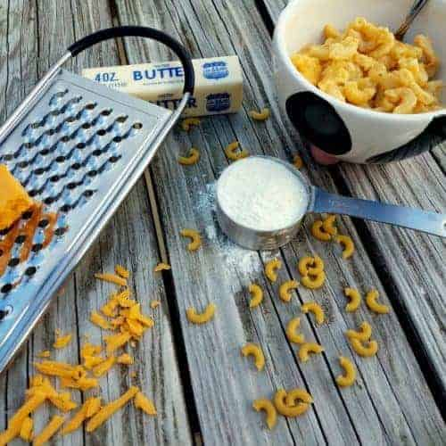 Macaroni and cheese (no cow's milk!) in a cow themed bowl on a picnic table. Adjacent to the bowl is a grater with a block of sharp cheddar on top, a measuring cup with flour, and a stick of butter. Sprinkled in the foreground is grated sharp cheddar cheese and uncooked macaroni.