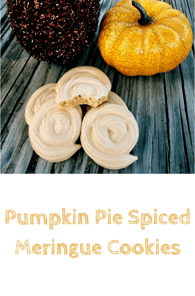 A loose pile of pumpkin pie spiced meringue cookies on a picnic table, with a sparkly brown and a sparkly yellow pumpkin in the background. This is the designated pinterest pin.