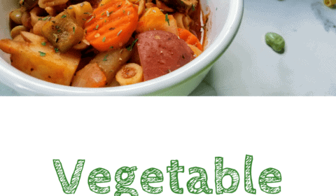 Vegetable ditalini soup served in a bowl. Bowl sits next to some of the raw ingredients and a large pan of the soup, all on a white marble background. This is the designated pinterest pin.