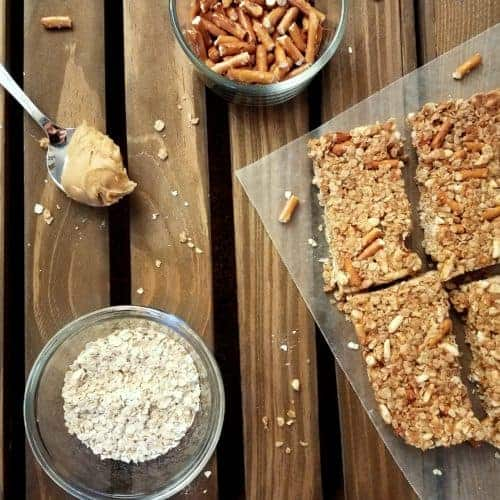 No-bake peanut butter oatmeal granola bars sit on a piece of wax paper on a dark wood plank background. Adjacent to the bars is a spoon with a scoop of peanut butter, a small glass bowl of pretzels, and a small glass bowl of oats. Oats and pretzel pieces are sprinkled about.