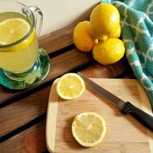 Lemon honey tea in a glass mug sitting on a coaster. On a small wooden cutting board rests a serrated knife and some lemon slices. In the background is a pile of lemons and a turquoise colored towel.