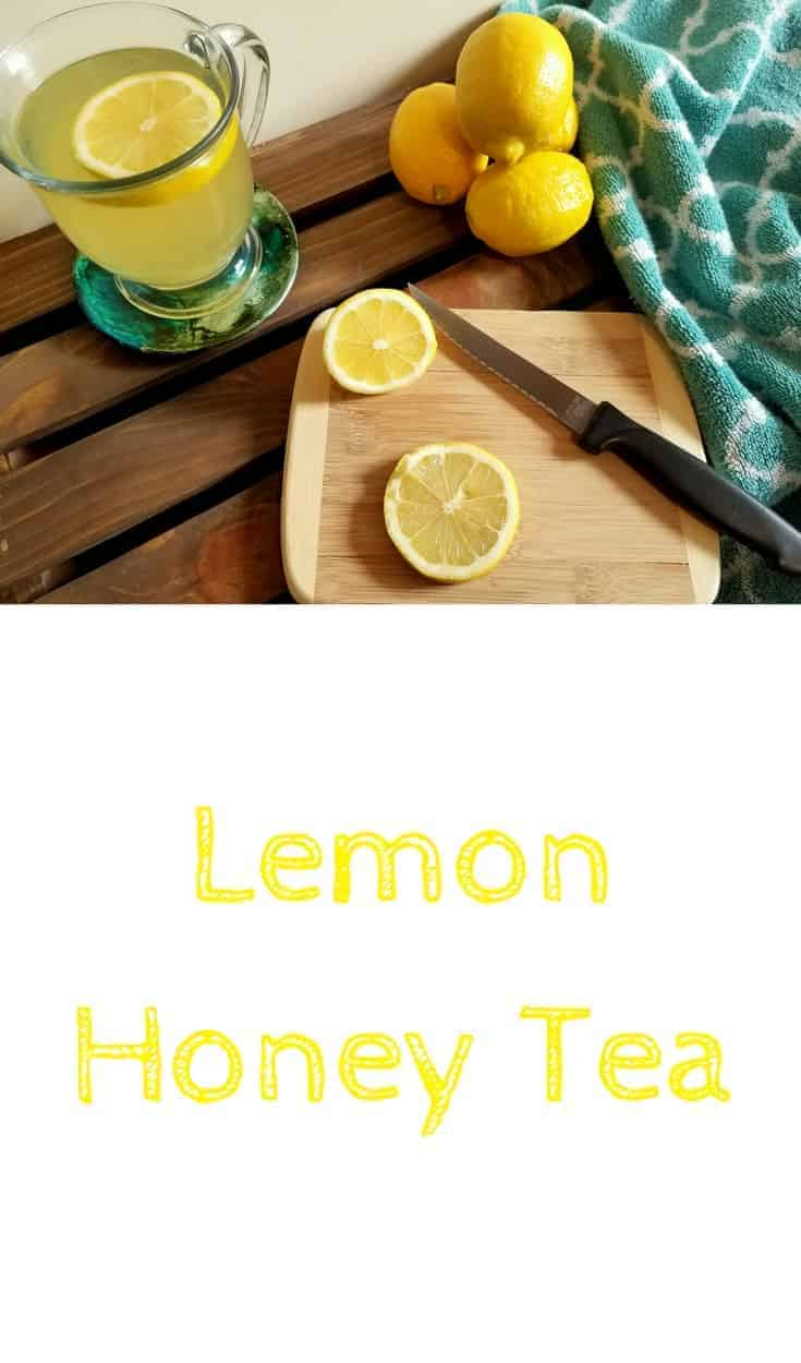 Lemon honey tea in a glass mug sitting on a coaster. On a small wooden cutting board rests a serrated knife and some lemon slices. In the background is a pile of lemons and a turquoise colored towel. This is the designated pinterest pin.
