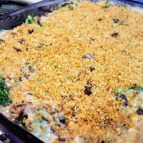 Broccoli, black bean, and cheesy wild rice casserole in a Pyrex baking dish on a stove.