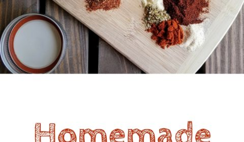 Piles of individual spices that make up homemade taco seasoning sit on a small cutting board on a dark wood plank background. Off to the side are measuring spoons and a small mason jar. This is the designated pinterest pin.