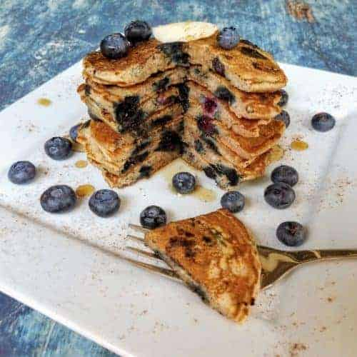 A stack of blueberry buttermilk pancakes on a square white plate sitting on a blue background. The pancakes are topped with a pat of homemade butter and are lightly drizzled with maple syrup.