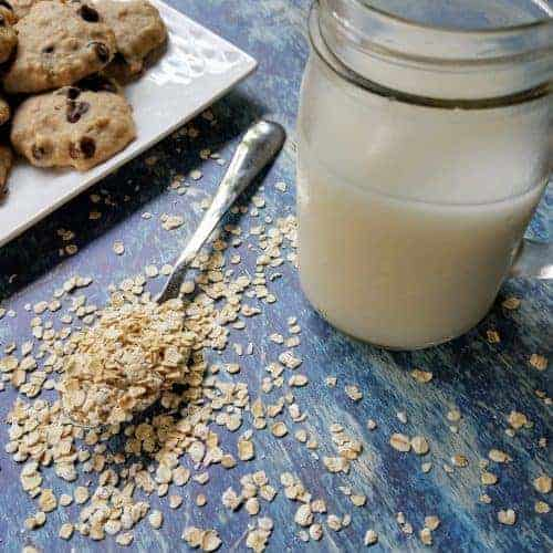 A mason jar filled with homemade oat milk sits on a blue background. A white plate of chocolate chip oatmeal pulp cookies sits in the upper left corner, and a spoon overflowing with uncooked oats sits next to the mason jar.
