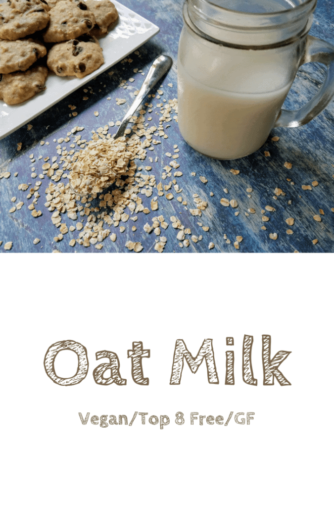 A mason jar filled with homemade oat milk sits on a blue background. A white plate of chocolate chip oatmeal pulp cookies sits in the upper left corner, and a spoon overflowing with uncooked oats sits next to the mason jar. This is the designated pinterest pin.