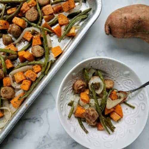 Roasted chicken sausage, sweet potato, onion, and green beans sit on an aluminum baking sheet. An unpeeled sweet potato sits in the upper right hand corner. In the lower right hand corner is a white bowl containing a portion of the roasted sausage and vegetable mixture. Everything sits on a white marble background.