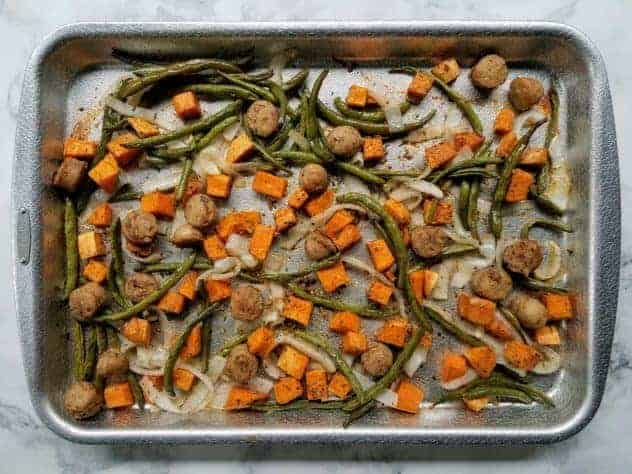 Roasted chicken sausage, sweet potato, onion, and green beans on an aluminum baking sheet on a white marble background.