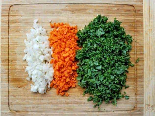 Diced carrots, onion, and roughly chopped kale on a light colored wooden cutting board.
