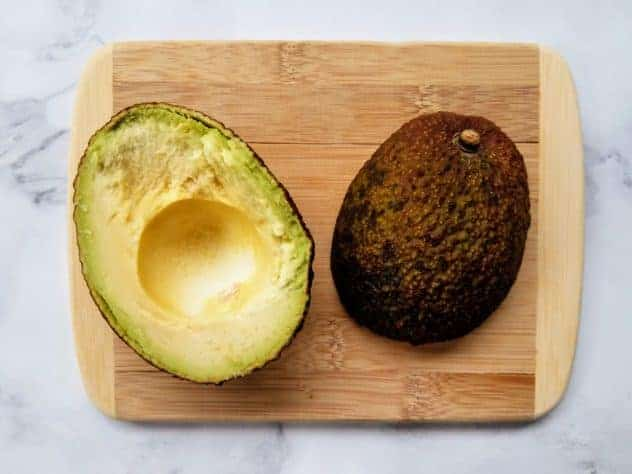 A halved avocado on a small wooden cutting board atop a white marble background.