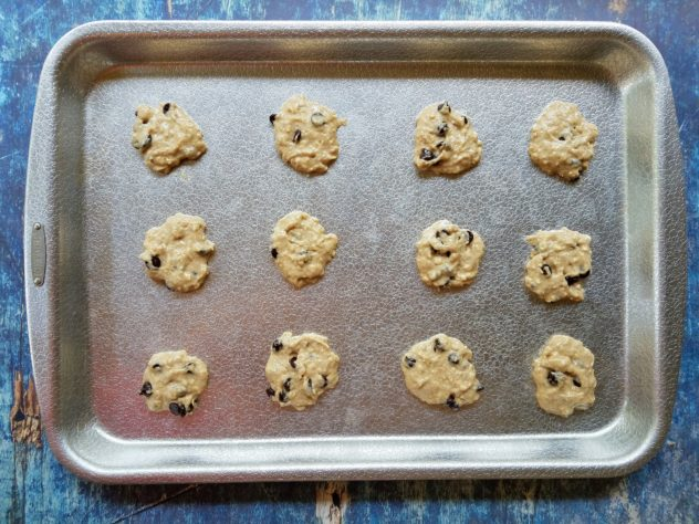 Rounded tablespoons of raw cookie dough on an aluminum baking sheet.