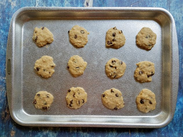 Freshly baked chocolate chip oatmeal pulp cookies on an aluminum baking sheet.
