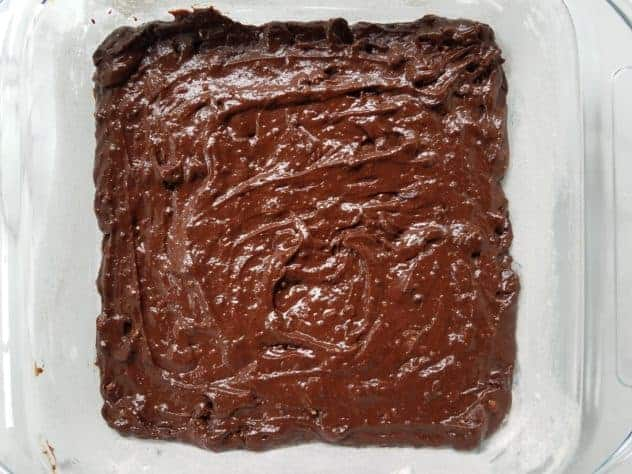 "Dark chocolate avocado brownie batter poured into a greased 8"" x 8"" glass pan."