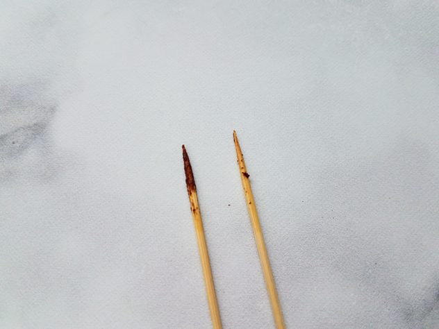 Two toothpicks side-by-side to illustrate under-cooked brownies (left toothpick) and thoroughly cooked brownies (right toothpick). The toothpick on the left looks like it was smeared in the batter and the toothpick on the right is mostly clear, except for a few crumbs of cooked brownie attached.