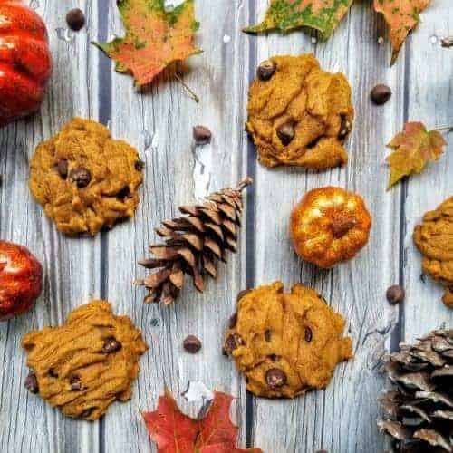 A collage of pumpkin chocolate chip cookies, pine cones, chocolate chips, leaves, and artificial pumpkins on a wood plank background.