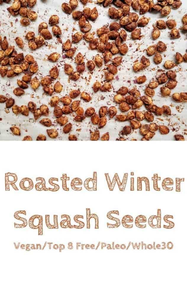 Fully roasted winter squash seeds coated with the spiced olive oil mixture sit on a parchment paper lined baking sheet. This is the designated pinterest pin.