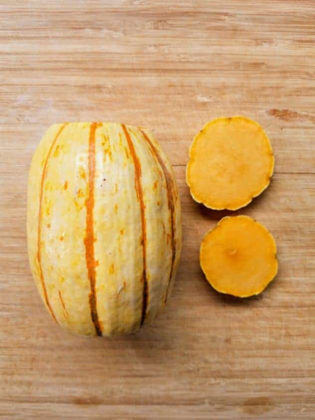 A delicata squash with the ends cut off sits on a wooden cutting board.