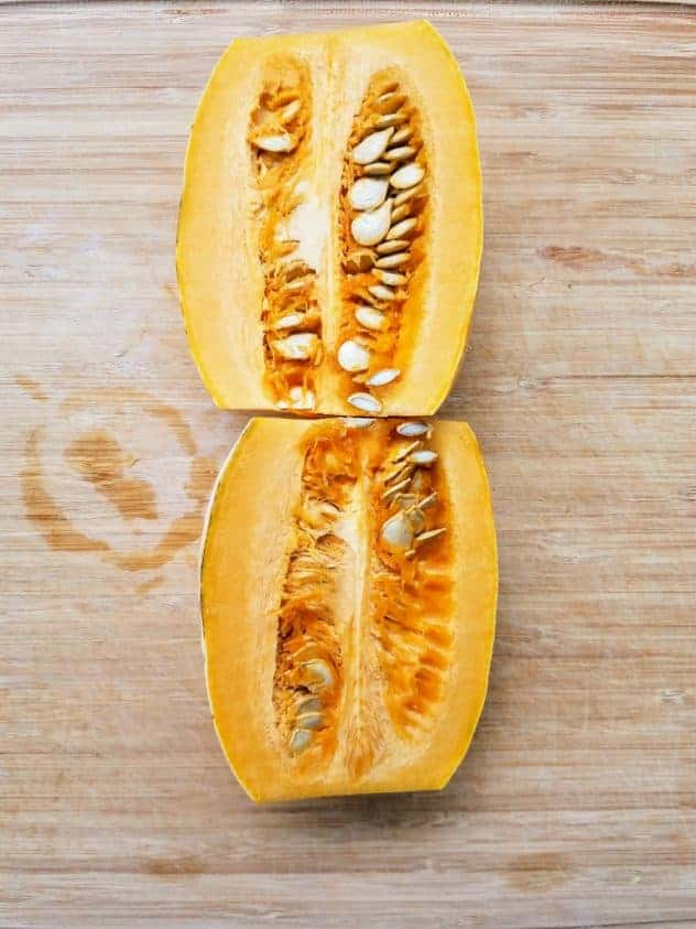 A delicata squash halved lengthwise sits on a wooden cutting board.