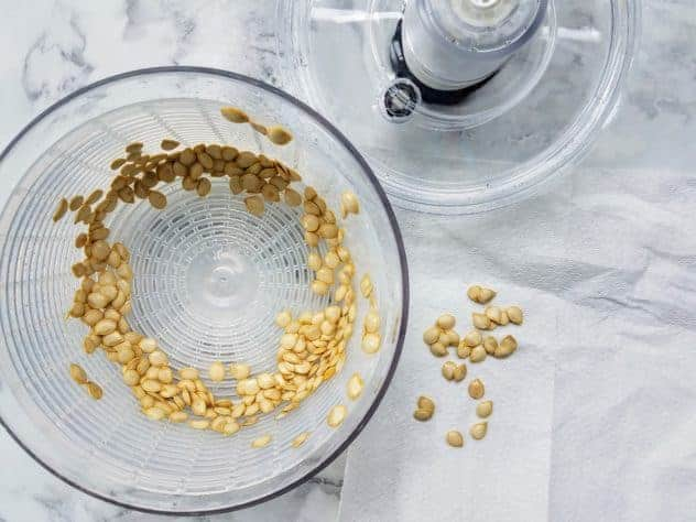 Rinsed winter squash seeds sit in a salad spinner after being spun dry. A few seeds sit on a paper towel. Background is white marble.