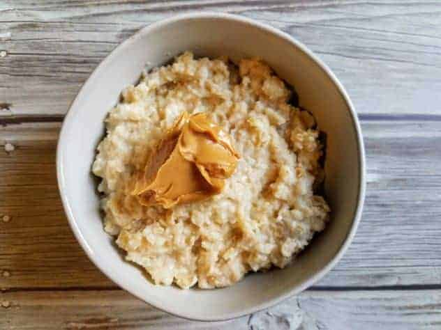 Microwave oatmeal topped with a dollop of creamy peanut butter in a small white bowl on a wooden background.