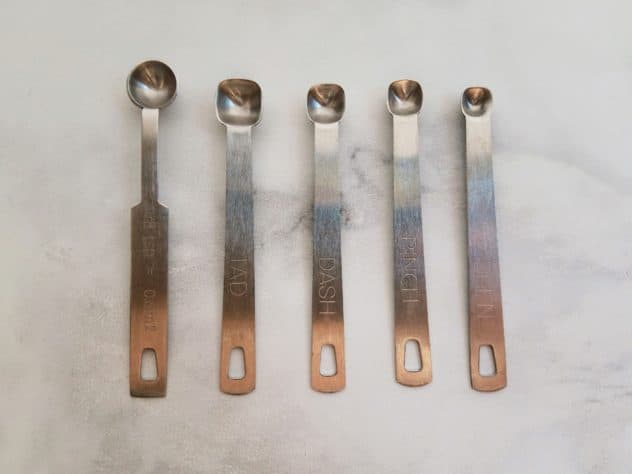 Side-by-side comparison of the 1/8, tad, dash, pinch, and smidgen measuring spoons. Spoons sit on a white marble background.