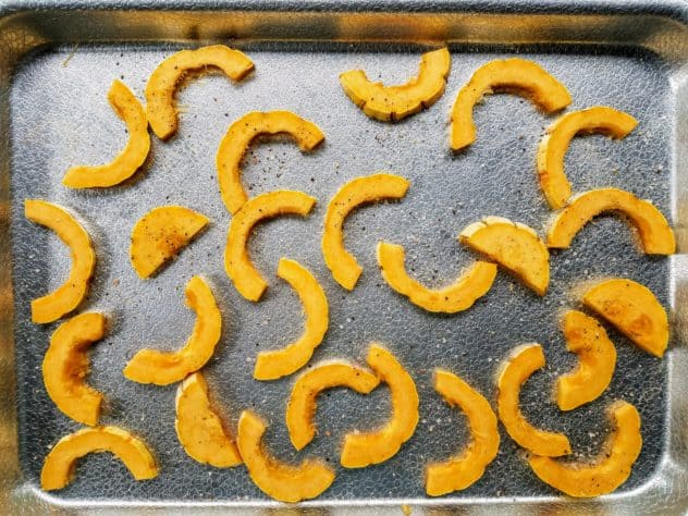Half moon shaped pieces of delicata squash spread out on a textured aluminum baking sheet. Pieces are topped with freshly ground Himalayan pink salt and freshly ground black pepper.