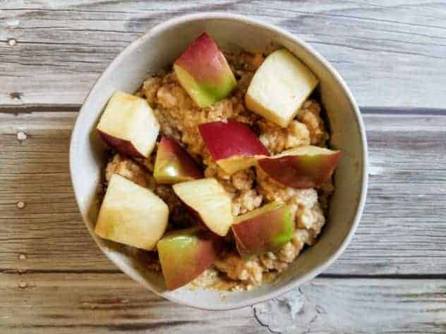 Microwave oatmeal with peanut butter, cinnamon, honey, and topped with chopped apple in a small white bowl on a wooden background.