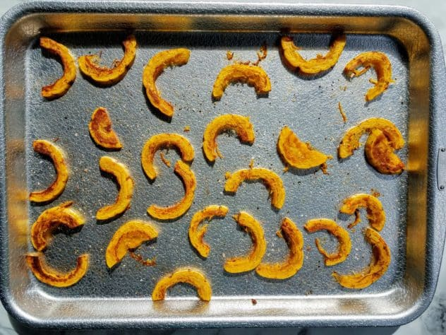 Half moon shaped pieces of delicata squash spread out on a textured aluminum baking sheet after halfway through roasting.