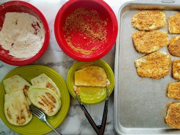 Starting from the upper left and moving clockwise: a medium-size red bowl holds flour, a medium-size red bowl holds homemade shake and bake, a textured aluminum baking sheet holds breaded eggplant slices, a small green bowl holds whisked eggs, and plain eggplant slices sit on a green plate. An eggplant slice is being dipped in egg using a pair of salad tongs.