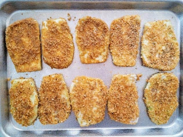 Breaded eggplant slices sit on a textured aluminum baking sheet.
