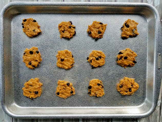Pumpkin chocolate chip cookies on a textured aluminum baking sheet prior to going in the oven.