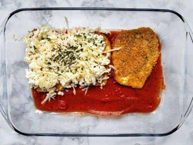"Example of the first layer: thin layer of tomato sauce on the bottom, then baked breaded eggplant slices, then grated mozzarella and parmesan cheeses topped with basil and parsley. Everything sits in a 9"" x 13"" glass pan on a white marble background."