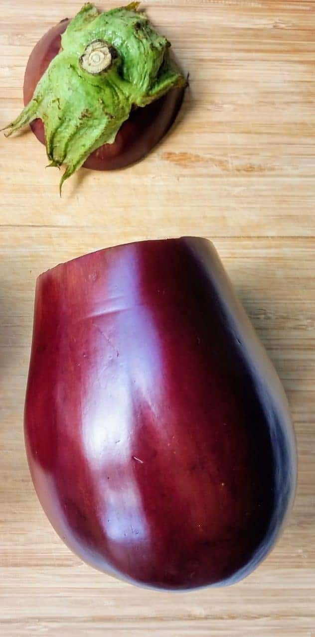 An eggplant sits on a wooden cutting board, with the stem end cut off.