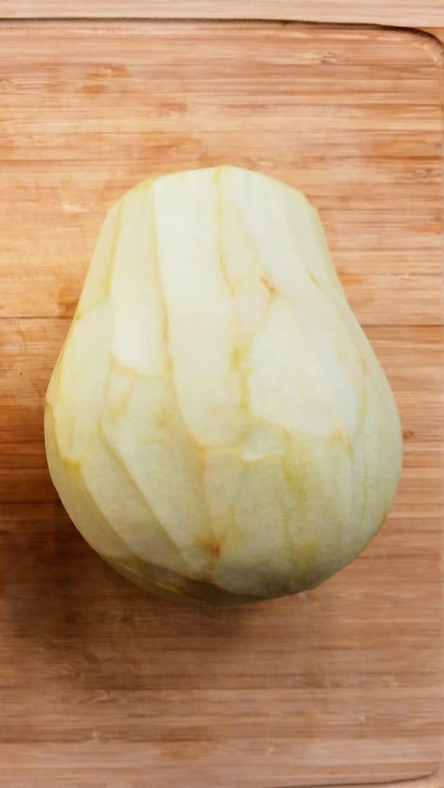 A peeled eggplant sits on a wooden cutting board, with the stem end cut off.