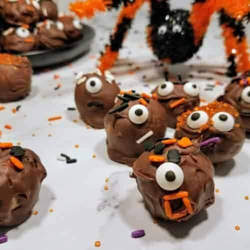 Monster faced chocolate peanut butter balls are being chased by a spider. A black plate with more chocolate peanut butter balls sits in the upper left. Everything sits on a white marble background and Halloween themed sprinkles are strewn about. This is the horizontal image.