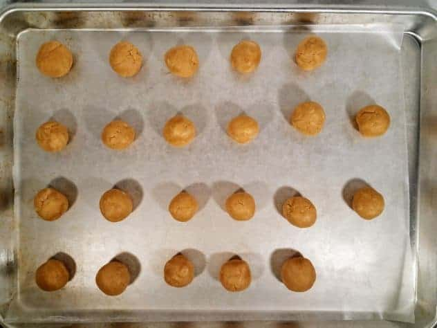 """3/4"""" uncoated peanut butter balls on a wax paper lined baking tray prior to refrigeration."""