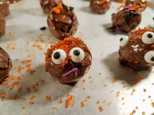 Halloween decorated chocolate peanut butter balls sit on a wax paper lined baking tray.