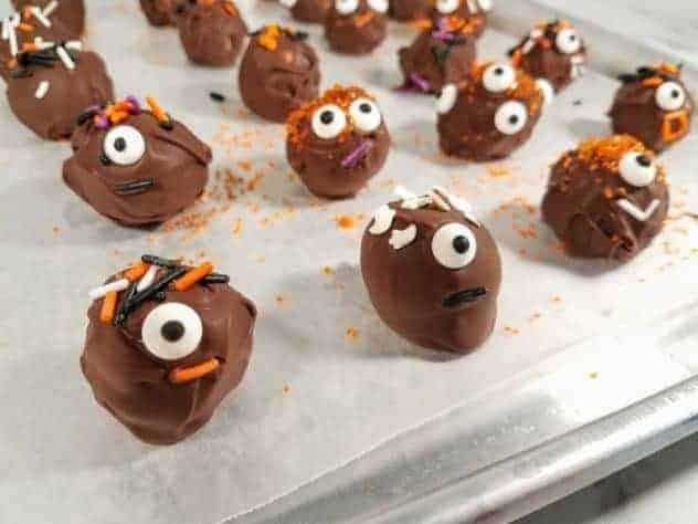 Halloween decorated chocolate peanut butter balls sit on a wax paper lined baking tray after refrigeration to harden chocolate.