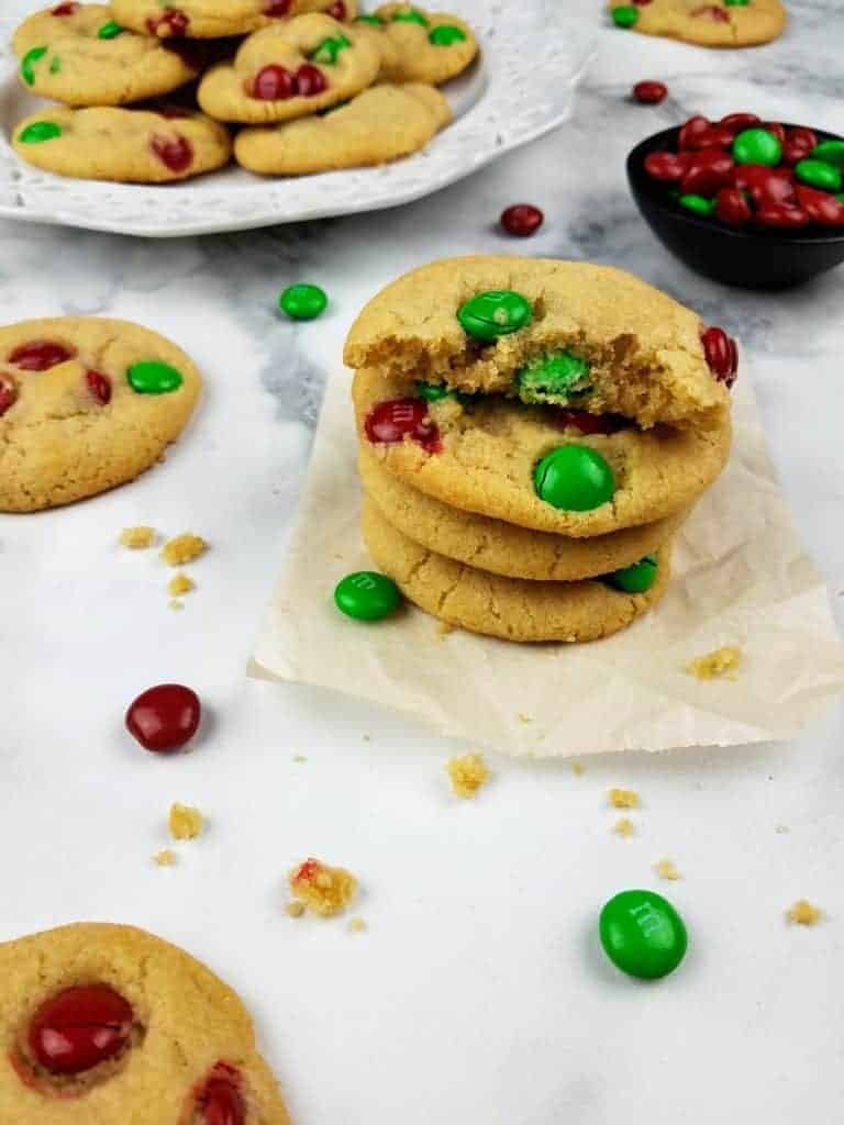A stack of M&M cookies sits on a square of parchment paper. The top cookie is broken in half to show the inside texture. In the background is a white plate with a pile of cookies and a small black bowl containing red and green M&Ms. Scattered about in the photo for texture are cookie crumbs, additional cookies, and red and green M&Ms. Everything sits on a white marble background. This is the vertical image.