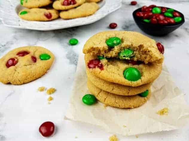 A stack of M&M cookies sits on a square of parchment paper. The top cookie is broken in half to show the inside texture. In the background is a white plate with a pile of cookies and a small black bowl containing red and green M&Ms. Scattered about in the photo for texture are cookie crumbs, additional cookies, and red and green M&Ms. Everything sits on a white marble background. This is the horizontal image.