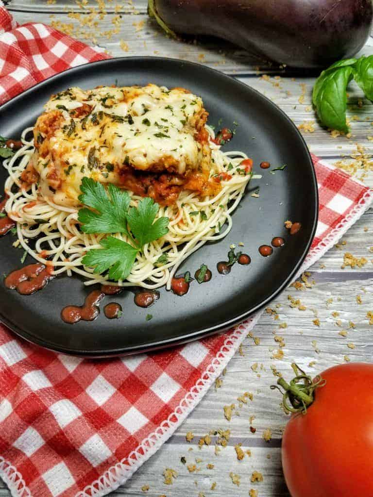 A slice of baked eggplant parmesan sits on a bed of angel hair pasta. The pasta is drizzled with tomato sauce, and garnished with a sprig of parsley. The entire thing sits on a round black plate, on top of a red/white checkerboard patterned kitchen towel. In the background is a tomato, eggplant, a sprig of basil, and some crumbs of homemade shake and bake. Peeking through the scene is also the wood plank background. This is the vertical photo.