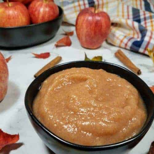 Applesauce sits in a small black bowl in the foreground. In the background is a large black bowl with gala apples and a striped tea towel. Scatted about are different colored leaves, gala apples, and cinnamon sticks. This is the horizontal image.