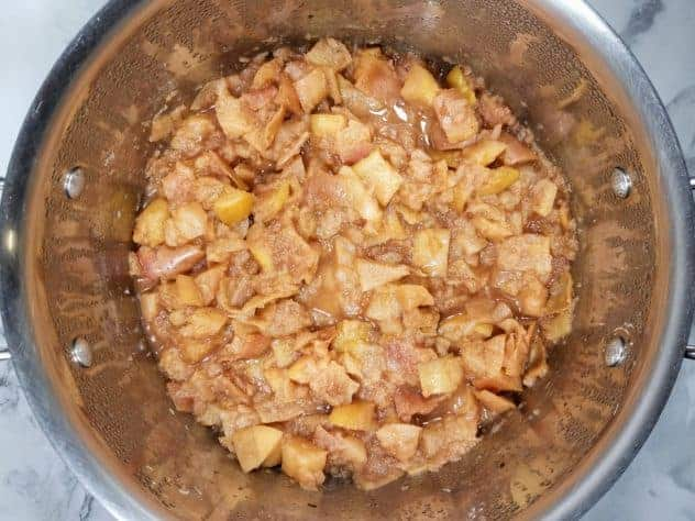 Chunky applesauce mixture in a stainless steel pot after cooking for 20-30 minutes.