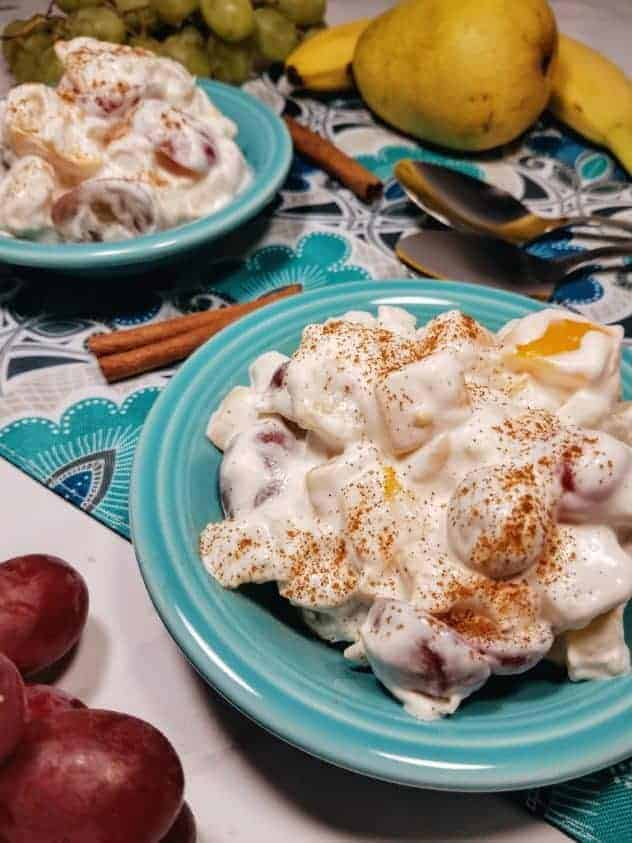 Whipped cream fruit salad topped with ground cinnamon sits in two teal colored fruit bowls. In the lower left is a handful of red grapes. In the background are two stainless steel spoons, a pear, a banana, and a bunch of green grapes. Two cinnamon sticks sit between the fruit bowls. Everything sits on a teal, navy, gray, black, and white colored paisley placemat which sits on top of a white marble background. This is the vertical image.