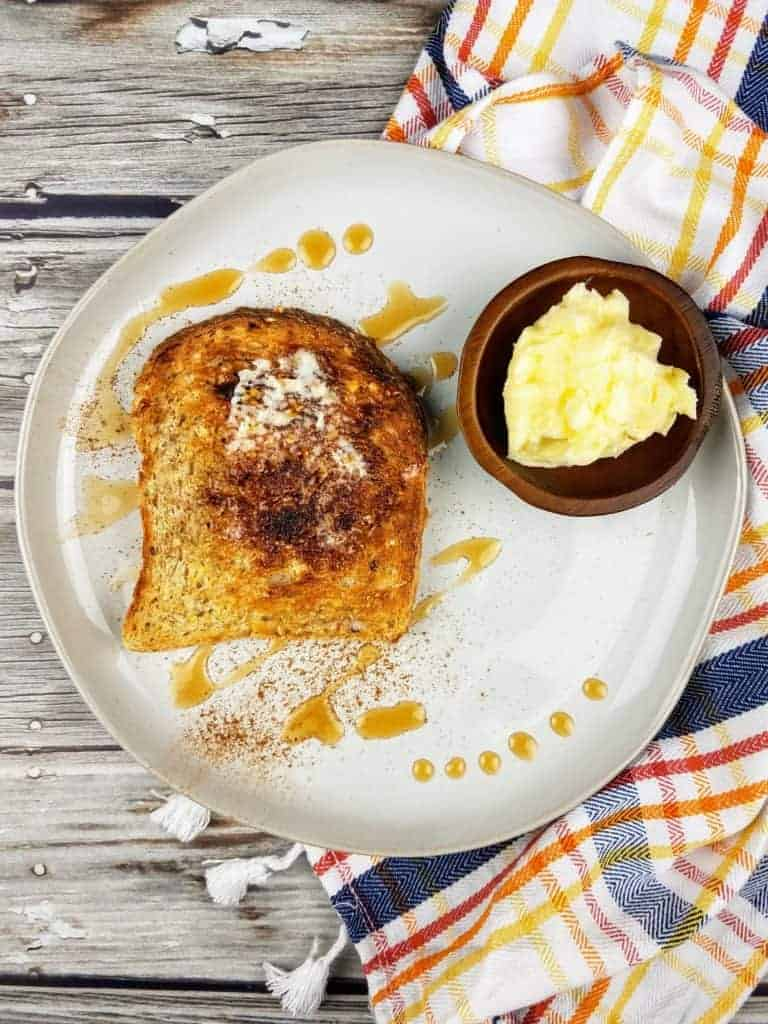 A dollop of homemade butter sits in a small dark wooden bowl on a white circular plate. Also on the plate is a piece of toast, slathered with homemade butter and topped with ground cinnamon and a few drizzles of pure maple syrup. Off to the side is a striped dish cloth with fringe. Everything sits on a wood plank background. This is the vertical image.