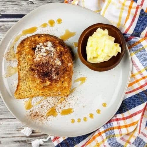 A dollop of homemade butter sits in a small dark wooden bowl on a white circular plate. Also on the plate is a piece of toast, slathered with homemade butter and topped with ground cinnamon and a few drizzles of pure maple syrup. Off to the side is a striped dish cloth with fringe. Everything sits on a wood plank background. This is the horizontal image.