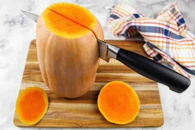 A butternut squash stands up on its end on a wooden cutting board, with a chef's knife partway down it lengthwise. The chef's knife is centered on the butternut squash. A striped dish towel sits in the upper right corner. Everything sits on a white marble background.