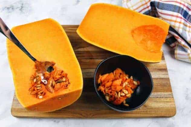 The two butternut squash halves sit side-by-side, one with its seeds scooped out and the other is in the process of having its seeds scooped. A small black bowl contains the scooped seeds. Everything sits on a wooden cutting board. A striped dish towel sits in the upper right corner. Everything sits on a white marble background.