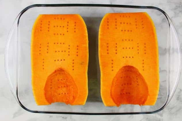 "The two butternut squash halves contain holes from a fork all over the flesh side. Both halves sit in a glass 9"" x 13"" pan, filled with a half inch of water."